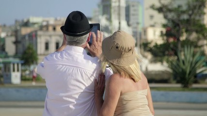Senior man and woman using tablet computer to take photo