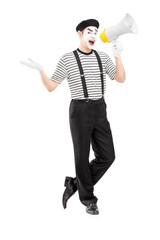 Full length portrait of a male mime artist speaking at loudspeak