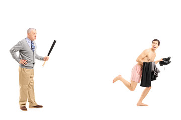 Middle aged man with baseball bat shouting at a young naked man