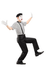 Full length portrait of a surpised mime artist gesturing with ha