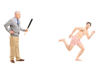 Angry middle aged man with baseball bat shouting at a shirtless