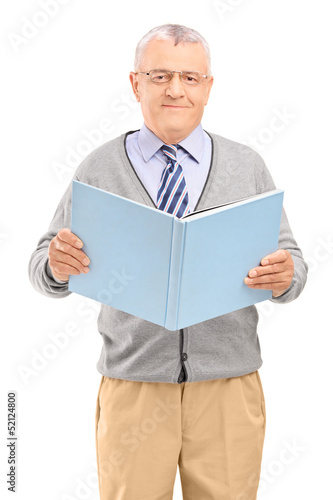 A middle aged gentleman holding a book and looking at camera