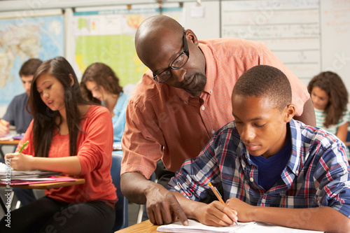 Teacher Helping Male Pupil Studying At Desk In Classroom - 52125692