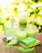 Quadro Cosmetics bottles and natural handmade soap on green background