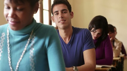 Portrait of happy hispanic man smiling during test at university
