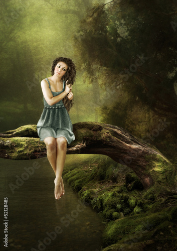 The girl sits on a tree over the water in the forest.