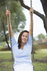 Happy Relaxed mature woman on swing outdoor