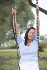 Relaxed mature woman on swing outdoor