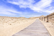 Wooden lane in the sand dunes with blue sky and clouds