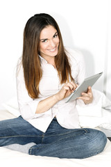 Beautiful smiling woman on sofa with tablet