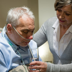 Nurse helping senior sick man with drinking