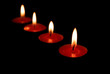 red candles burning in a dark space