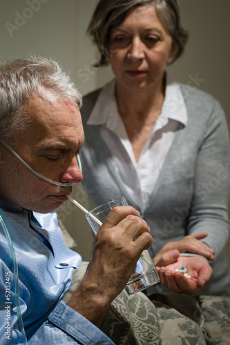 Caring senior wife holding drugs for husband