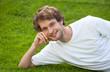 Student liegt auf der Wiese und lächelt