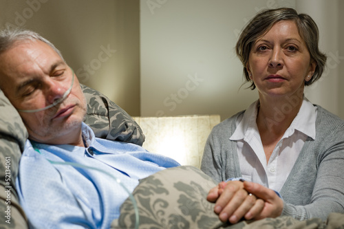 Caring wife holding sick senior husband's hands