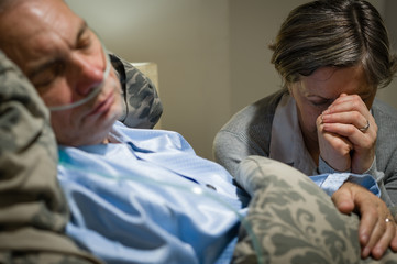 Old wife praying for terminally ill husband