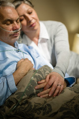 Loving elderly couple sleeping in bed