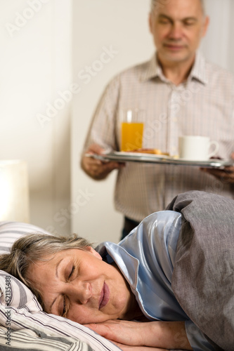 Loving senior husband serving breakfast to wife