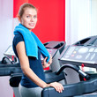 Young woman at the gym run on on a machine
