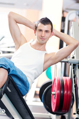 Young man doing exercises at gym