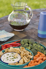 Dip with pita chips, vegetables and iced tea served outdoors