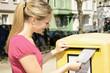 Junge Frau wirft Brief in Briefkasten
