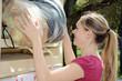 Junge Frau wirft Altkleider in Container