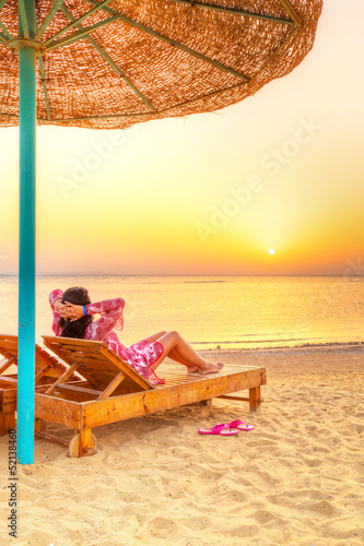 Relax under parasol on the beach of Red Sea at sunrise