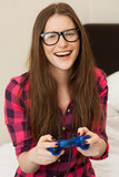 Young woman in casual playing videogame poster