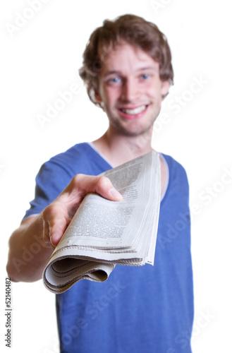 Junger Mann reicht die Tageszeitung