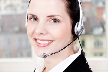 Junge brünette Frau arbeitet in einem callcenter mit headset