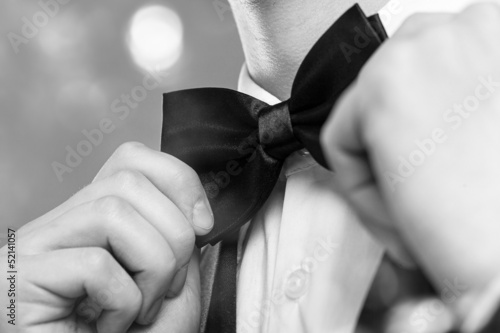 Man's hands touches bow-tie