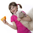 a happy little girl with a sheep and a cheese