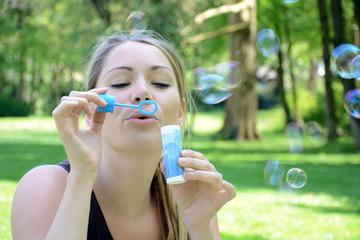 Junge Frau pustet Seifenblasen