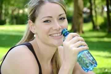 Junge Frau trinkt Wasser im Park