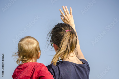 Mum and son waving