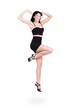 Jumping woman in little black dress on white