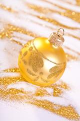 Golden Christmas toy whit handmade decoration. Spilled glitter