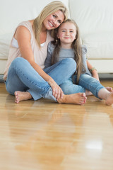 Mother and daughter sitting on the floor embracing