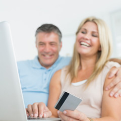 Couple using laptop on the sofa to shop online
