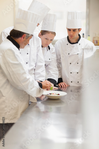 Trainees listening to the head chef