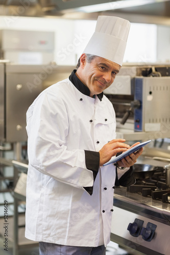 Smiling chef using digital tablet
