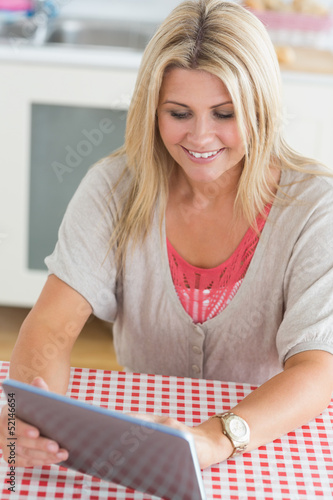 Laughing young woman working on tablet