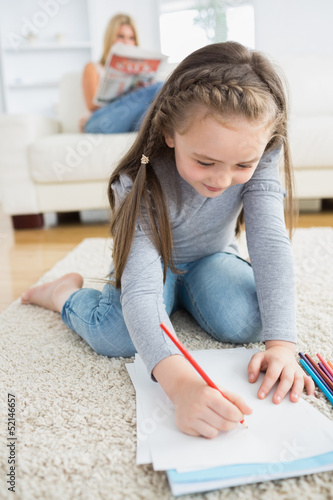 Little girl drawing sitting on floor with mother reading