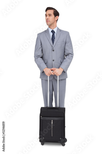 Serious businessman waiting with his luggage