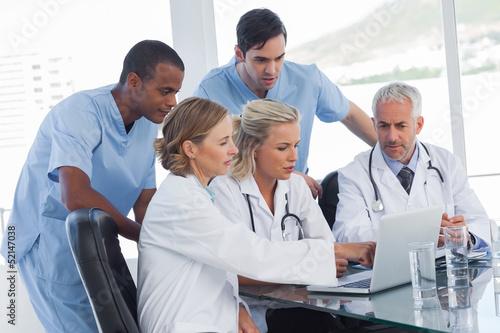Leinwandbild Motiv Serious medical team using a laptop