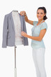 Fashion designer measuring blazer lapel on mannequin and smiling