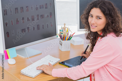Editor using graphics tablet to edit and smiling