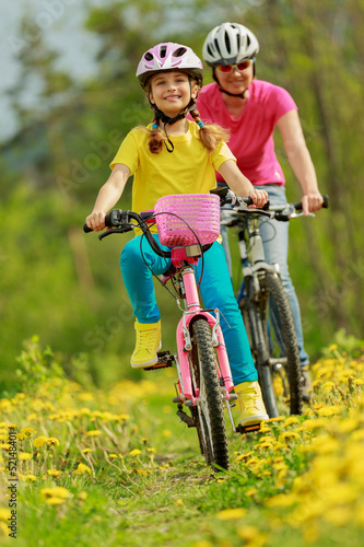 Bike riding -  girl with mother on bike, active family concept
