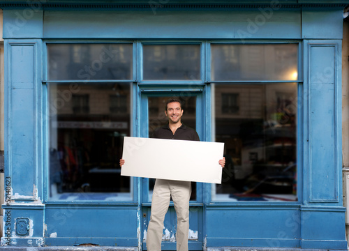 Man with sign by shop